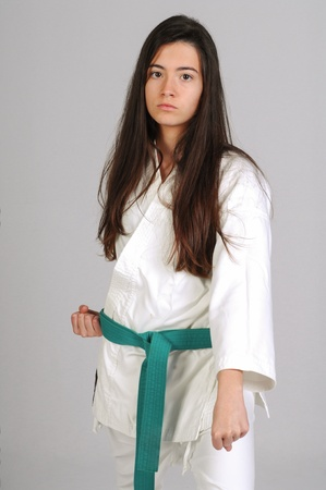 girl in Karate moves on grey background photo