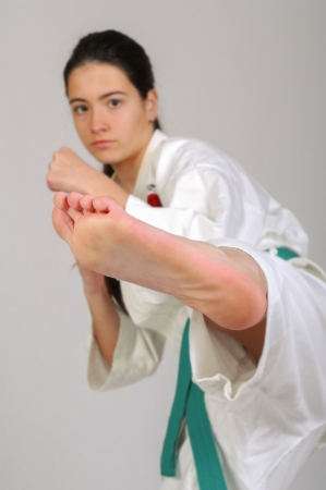 girl punch: girl in Karate moves on grey background