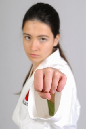 karateka: girl in Karate moves on grey background