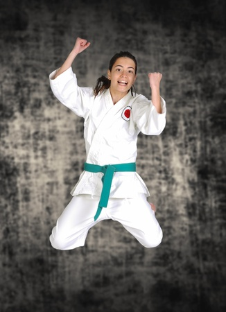 beautiful karate girl in a happyness jumping photo