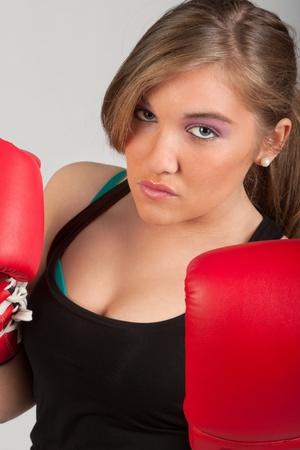 combative: beautiful girl training combat with boxe glaves, studio photo