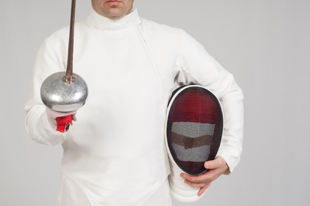 fencer athlete with sword and mask over grey background photo