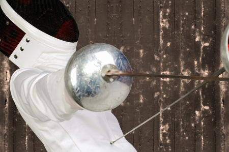 fencer athlete with sword and mask in action photo