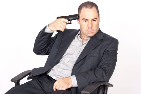 Suicide concept -  man pointing a gun at his head, white background photo
