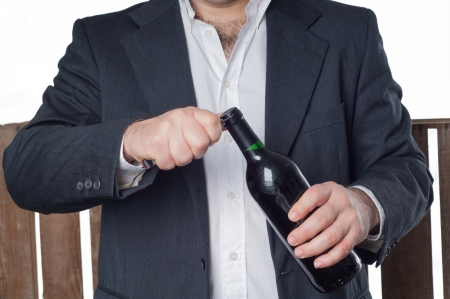 Detail of a man opening a red wine bottle