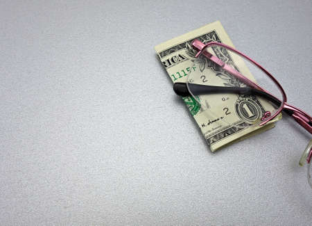 one US dollar banknote and glasses on a gray background