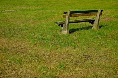 empty bench: green grass and empty bench seating behind Stock Photo