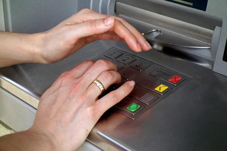 cuenta bancaria: mano de la mujer cubre su mano al introducir el PIN en un cajero automático