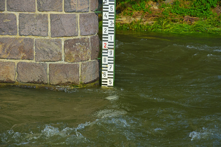 depth measurement: Stone pillar and water level meter on the river