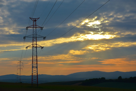 isolator: Electric mast, high voltage wires, and sunset Stock Photo