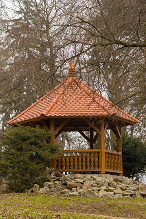 arbor with red roof built on stones