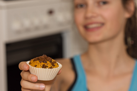 girl offers freshly baked muffin with fruit Imagens