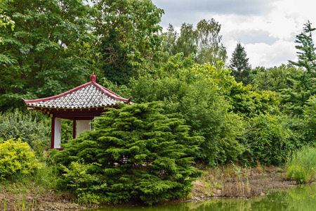 Japanese wooden gazebo in a park on the edge of the lake