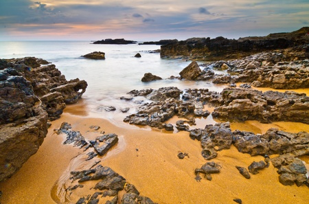 silk screen: Beautiful panoramic view of secluded beach in Asturias, Spain at sunset  Stock Photo