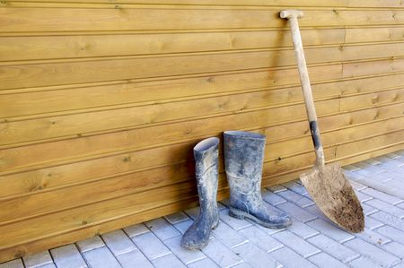 gumboots: Shovel and gumboots based on a wooden wall Stock Photo