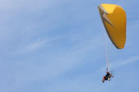 Orange paramotoring with blue sky photo