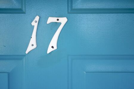 seventeen: number seventeen nailed to a wooden door blue; Merced; California; Usa