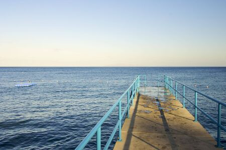 literally: pier at sunset on a calm blue sea