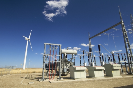 substation: high-voltage substation and windmill with blue sky in Spain Stock Photo