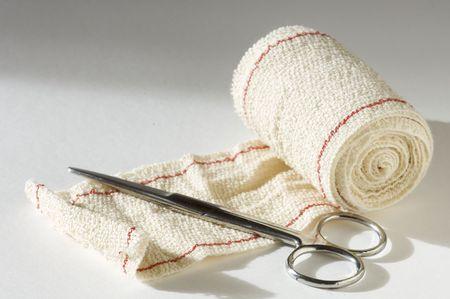herida: tijeras m�dicas y vendas con fondo blanco  Foto de archivo