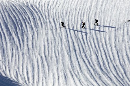three climbers crossing a snowfield in the Pyrenees photo