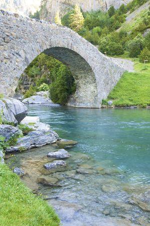 arcos de piedra: Puente de piedra sobre un r�o en la monta�a de Pyrenees  Foto de archivo