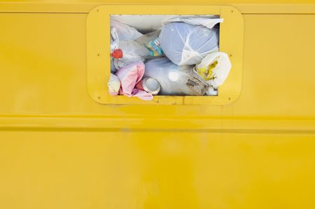 Detail of a yellow recycling container overflowing photo