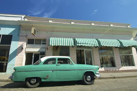 stingrays: old green car parked in a typical street of Cienfuegos