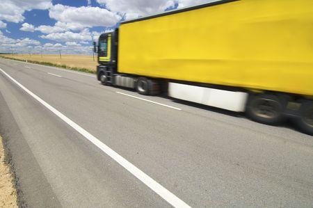 circulating yellow truck speeding along a straight road photo