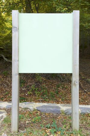 green signboard in a forest photo