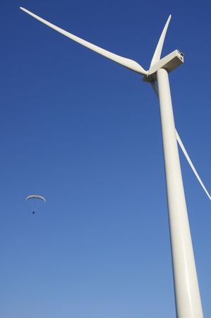 Paraglide and wind mill with blue sky photo