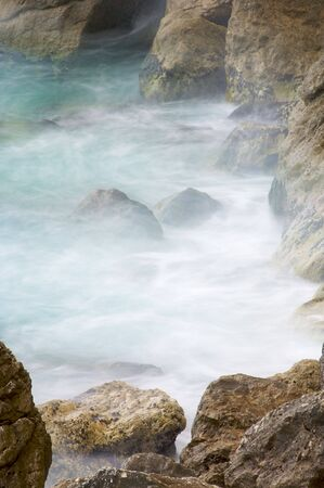 Rocks in water at the Mediterranean coast photo