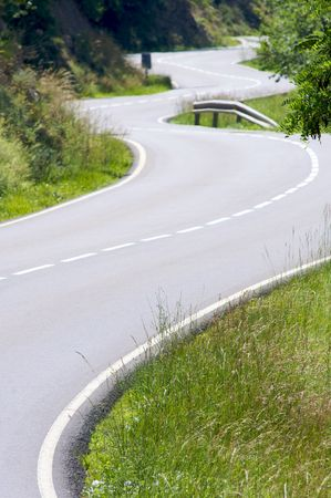 twisty: twisty road and grass on the roadside Stock Photo