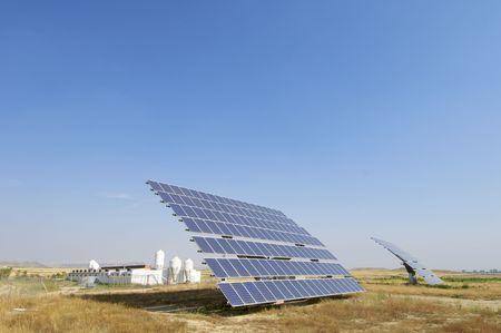 Solar field with blue sky and farm photo