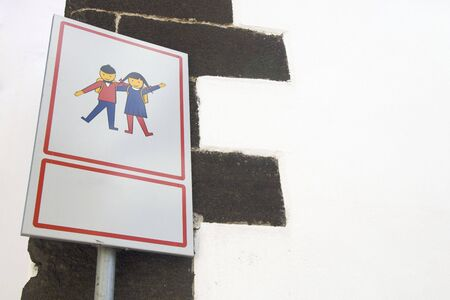 basic care: white metal sign with schoolchildren Stock Photo