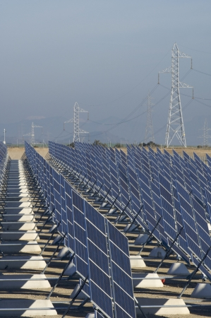 electric cell: huge solar station and high tension tower Stock Photo