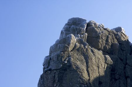 rocky pinnacle with frost and blue sky photo