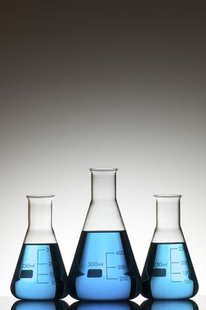 three flasks with liquid blue and white background Stock Photo - 6467552