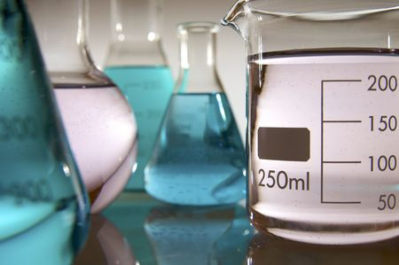 forefront: forefront of a group of beakers with pink and blue-green liquid Stock Photo
