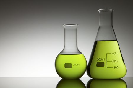 two flasks with liquid bright green and white background photo