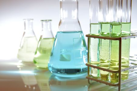 test tubes and flasks with green and blue liquid in a laboratory photo