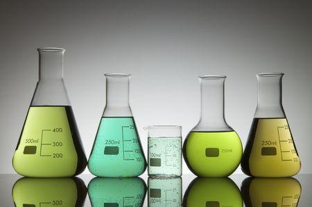 greenish: group of glasses and bottles with greenish liquid laboratory