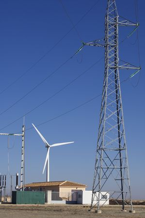 high-voltage substation and windmill with blue sky photo