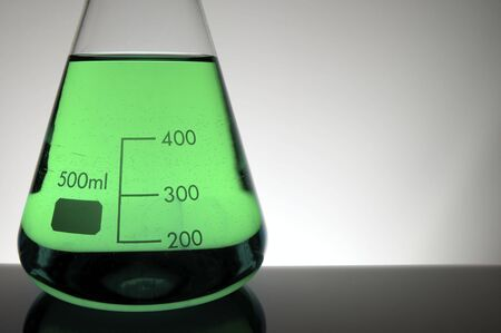 scientifical: detail of a beaker with green liquid and white background
