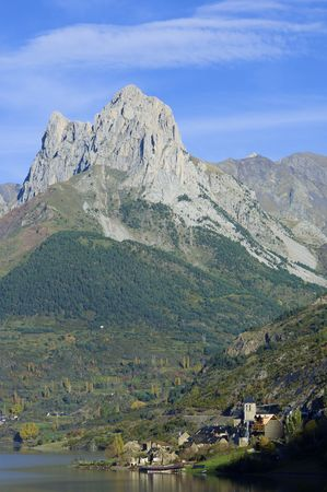 rocky peak near a lake village in the Pyrenees, Spain photo