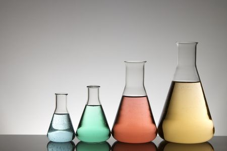 group of four flasks with colored liquid and a white background photo