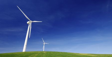 Modern windmills on a green hill with blue sky photo