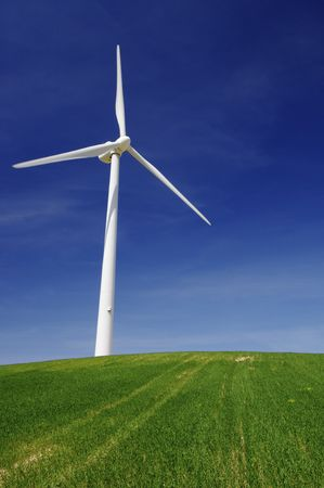 Modern windmill on a green hill with blue sky Stock Photo - 6779246