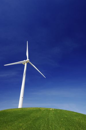 Modern windmill on a green hill with blue sky Stock Photo - 6779249