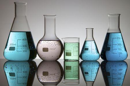 cristalería: cinco frascos de laboratorio con l�quido y un fondo blanco  Foto de archivo